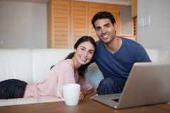Smiling couple using a laptop while having a tea Royalty Free Stock Photo