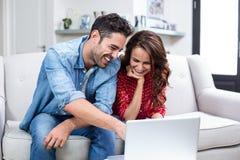 Smiling couple using laptop Royalty Free Stock Photos