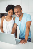 Smiling couple using laptop in kitchen Stock Images