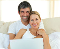 Smiling couple using a laptop lying in the bed Royalty Free Stock Photography