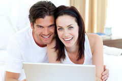 Smiling couple using a laptop lying on their bed Stock Photo