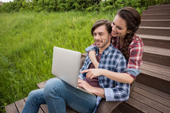 Smiling couple using laptop while sitting on stairs at park Stock Photography
