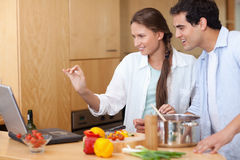 Smiling couple using a laptop to cook Stock Photo