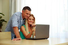Smiling couple using laptop together. At home Stock Photo