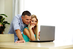 Smiling couple using laptop together Stock Images