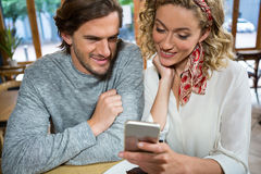 Smiling couple using mobile phone at table in cafe Royalty Free Stock Images