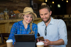 Smiling couple using mobile phone at table in cafe Royalty Free Stock Photos