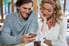 Smiling couple using smart phone at table in cafe Stock Photography