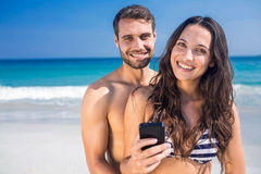 Smiling couple using smartphone at the beach Stock Photo