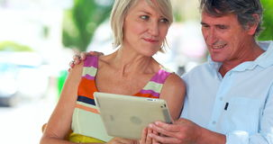 Smiling couple using a tablet. In a cafe outside stock video footage