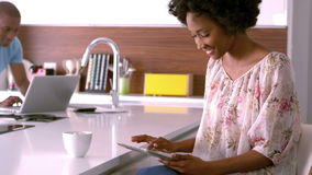 Smiling couple using tablet and laptop. Handsome man using tablet in the kitchen in slow motion stock video