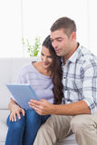 Smiling couple using tablet PC Royalty Free Stock Image