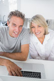 Smiling couple using their laptop in the morning looking at came Stock Photo
