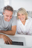 Smiling couple using their laptop in the morning Royalty Free Stock Photos
