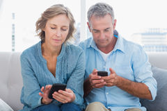 Smiling couple using their smartphones Royalty Free Stock Image