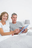 Smiling couple using their tablet pc to buy online Royalty Free Stock Images