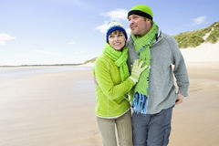 Smiling couple walking on cold beach together Royalty Free Stock Image