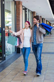Smiling couple walking hand in hand and going window shopping Stock Image