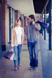 Smiling couple walking hand in hand with shopping bags Stock Photo