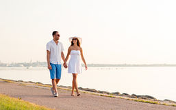 Smiling couple walking outdoors. Love, travel, tourism, summer and people concept - smiling couple on vacation wearing sunglasses and holding hands walking at Royalty Free Stock Images