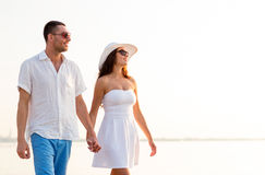 Smiling couple walking outdoors. Love, travel, tourism, summer and people concept - smiling couple on vacation wearing sunglasses and holding hands walking at Stock Images