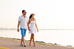 Smiling couple walking outdoors. Love, travel, tourism, summer and people concept - smiling couple on vacation wearing sunglasses and holding hands walking at Royalty Free Stock Photography