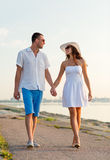 Smiling couple walking outdoors. Love, travel, tourism, summer and people concept - smiling couple on vacation wearing sunglasses and holding hands walking at Royalty Free Stock Photos