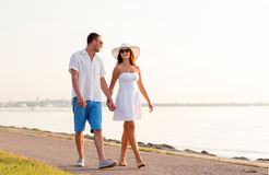 Smiling couple walking outdoors. Love, travel, tourism, summer and people concept - smiling couple on vacation wearing sunglasses and holding hands walking at Stock Photo