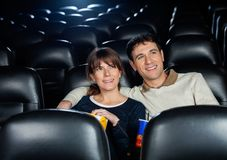 Smiling Couple Watching Film In Theater Stock Photo
