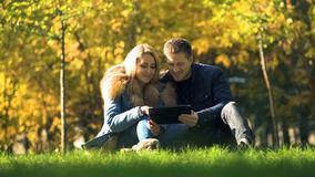Smiling couple watching photos on tablet, sitting in beautiful autumn park stock photography