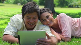 Smiling couple watching a tablet computer stock footage