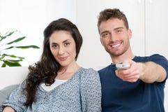 Smiling couple watching tv stock photo