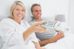 Smiling couple watching tv in bed Royalty Free Stock Photography
