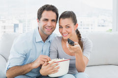 Smiling couple watching tv on the couch with bowl of popcorn Stock Images