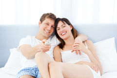 Smiling couple watching tv at home Royalty Free Stock Photos