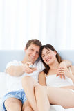 Smiling couple watching tv at home Stock Photos