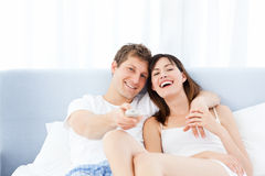Smiling couple watching tv at home Stock Photo