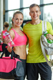 Smiling couple with water bottles in gym Royalty Free Stock Photography
