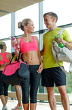 Smiling couple with water bottles in gym Royalty Free Stock Images