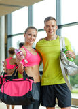 Smiling couple with water bottles in gym Stock Photography