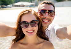 Smiling couple wearing sunglasses making selfie Stock Photos