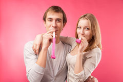 Smiling couple with whistles hugging Stock Photo
