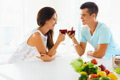 Smiling couple with wine and vegetables in kitchen Royalty Free Stock Photo