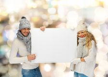 Smiling couple in winter clothes with blank board Stock Photography