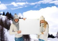 Smiling couple in winter clothes with blank board Royalty Free Stock Photography