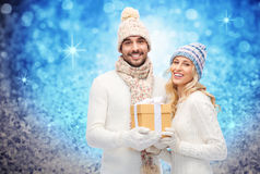 Smiling couple in winter clothes with gift box Stock Photos