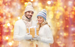 Smiling couple in winter clothes with gift box Royalty Free Stock Photos
