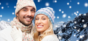 Smiling couple in winter clothes over mountains Royalty Free Stock Photography