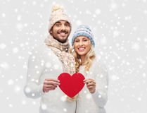Smiling couple in winter clothes with red heart Stock Image