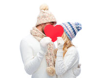 Smiling couple in winter clothes with red heart. Love, valentines day, couple, christmas and people concept - smiling men and women in winter hats and scarf Royalty Free Stock Images